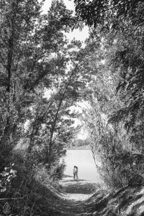 Hiking trail engagement image in black and white from Forlì Lake, Forlì-Cesena, Italy, of the couple kissing in nature