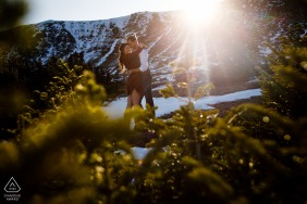 Mountain sunburst couple engagement portraits at Loveland Pass, CO, the sun flares the lens as it quickly disappears behind the ridge