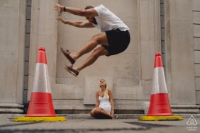 England playful street engagement photography in London of groom jumping over bride