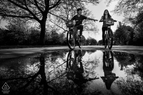 Black and white bike engagement of the couple biking on a rain water reflection in London, United Kingdom