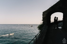 E-session of couple silhouetted and framed in archway by the water in positano