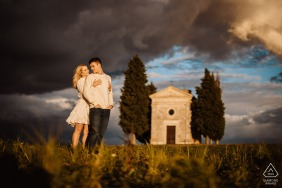 E-shoot of a couple standing at the sunset with the chapel of vitaleta on their background