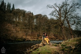 Bolton Abbey, Yorkshire, UK Engagement portrait shoot image showing the couple kissing while sitting on a tree stump