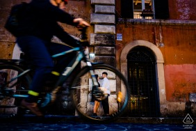 Rome Couple kissing with a moving, passing bike in the foreground during photoshoot in Italy