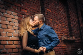 Zrodliska Park, Lodz, Poland lovers hug each other against the red brick wall