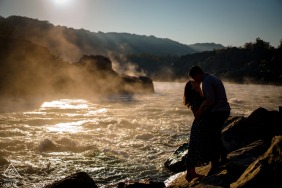 The couple kiss in silhouette with the early morning light and fog down river from them at their Great Falls, Virginia engagement portrait session