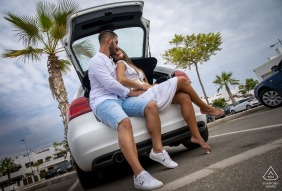 Águilas - Spain engaged couple Speaking in car during their parking lot photo session under a palm tree