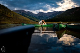 Newly engaged couple share a kiss while in a canoe on Piney Lake during their engagement session