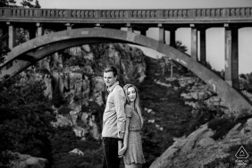 CA pre-wedding photo session with an engaged couple standing back to back under the arch of Rainbow Bridge in California