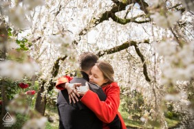 France engagement photoshoot & pre-wedding session in the Japonese garden at Toulouse, France with A couple kissing while spring blow