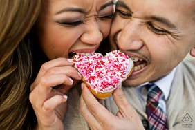 CA engagement portrait with a posed couple eating at the San Jose City Hall Rotunda with some Sweet Donut Love