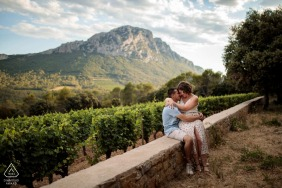 FR pre wedding portrait session with engaged lovers at Domaine de L'Hortus South of France with a couple sitting on a low wall