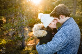 California pre wedding and engagement photography from the trees of Lake Tahoe, CA with a warm sunset light glowing on a man and woman on a cold fall afternoon in a pine forest