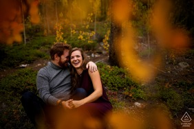 Colorado pre wedding and engagement photography in Keystone, CO of the couple laughing while sitting on the forrest floor during their fall engagement photos in Summit County