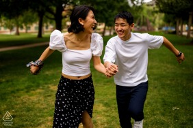 CO engagement photo shoot of a couple laughing while running at the Colorado School of Mines