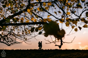 United Kingdom pre wedding and engagement photography at Lyme Park, Manchester of a Couple silhouetted on horizon with tree foreground