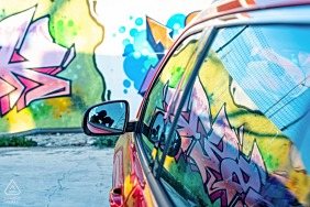 Spain pre-wedding photo session with an engaged couple in Úbeda, Jaén with a car reflecting colorful graffiti