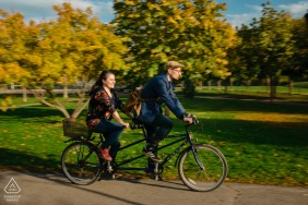 Canada pre wedding and engagement photography at Parc Laurier, Montreal, Quebec with a couple riding on a tandem bike through a park - they met when he was a bike messenger and made a delivery to her office