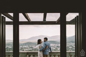 GR engagement photoshoot & pre-wedding session in Athens, Greece of a couple standing on a balcony with great view