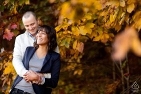 MA engagement portrait with a posed laughing couple in the fall leaves of Boston, Massachusetts