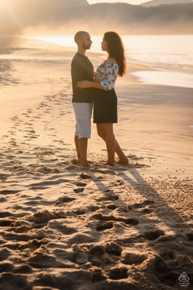 Brazilian engagement portrait with a posed couple standing on the beach sands of Niteroi - RJ Brazil When the sun kisses a backlit image