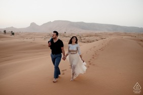 UAE pre wedding and engagement photography from Maleiha Desert, Dubai of a couple walking and Exploring the desert