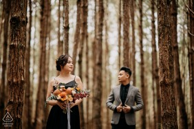 Vietnam forest pre-wedding photo session with an engaged couple holding flowers while standing in the trees of Dalat