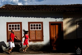 Brazil engagement portrait with a posed couple running through the streets of Cidade de Goiás holding hands in red shirts