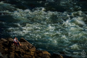 Virginia pre wedding and engagement photography of The couple sitting by the raging river at Great Falls