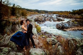 Virginia engagement photo shoot of The couple embracing on a high cliff at Great Falls