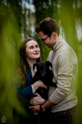District of Columbia pre wedding and engagement photography in Washington DC of A couple embracing with their puppy under a willow tree