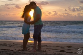 FL sunset engagement portrait with a posed couple at Fort Lauderdale Beach in Florida embracing on the beach