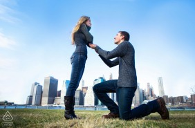 NY engagement photoshoot & pre-wedding picture showing a proposal during their engagement session at Brooklyn Bridge Park