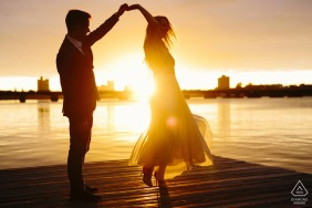 Charles River Engagement Session with couple dancing at sunset on the dock by the water