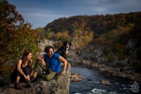 Verlobungspaar des Great Falls National Park mit einem Hund während eines vorehelichen Fotoshootings