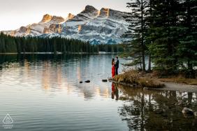 Una pareja de Two Jacks Lake, AB, Canadá disfrutando de una hermosa mañana y de las vistas durante una sesión de fotos de compromiso.