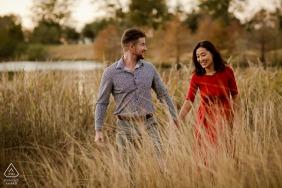 Mini sessão fotográfica de Katy, TX antes do dia do casamento com o casal se divertindo em um parque natural de grama alta