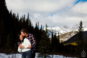 Keystone, CO outside forest picture session before the wedding day with some fun Winter cuddles in the snow