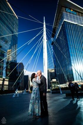 Denver, Colorado, uma pequena foto urbana antes do dia do casamento com um casal compartilhando um beijo na Millennium Bridge