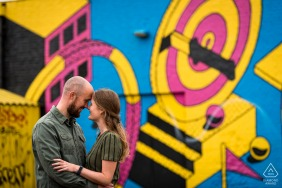 Breda mini urban pic shoot before the wedding day showing the couple is posing on the background you see a graffiti wall