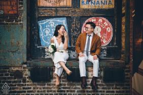 Mini foto urbana em Chicago antes do dia do casamento com um casal sentado em uma doca de carregamento de caminhão e brincando