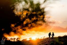 Posbank mini-sihouetted sessão de fotos de casal antes do dia do casamento no pôr do sol durante uma caminhada juntos