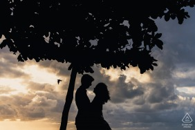 Maceió sunset beach image session before the wedding day using a Silhouette of a couple under a tree
