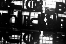 Pequena sessão de fotos internas em Chicago com o casal antes do dia do casamento se beijando em frente a uma grande pilha de cartas de letreiros arquitetônicos