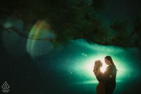 Mini-sessão de fotos artísticas do casal em Boulder antes do dia do casamento, resultando em um retrato iluminado em frente a uma torre de água texturizada