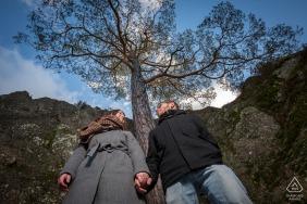 Sessão de fotos ao ar livre do casal Rocher du Falkenstein antes do dia do casamento, mostrando um ângulo de câmera baixo com uma árvore solitária centralizada