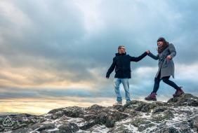 Mini-sessão fotográfica de casal na praia Rocher du Falkenstein antes do dia do casamento caminhando sobre as rochas no tempo frio