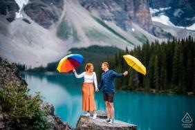 Lago Moraine, Parque Nacional de Banff, AB, Canadá micro sessão de fotos ao ar livre na montanha antes do dia do casamento, no topo de uma rocha com guarda-chuvas coloridos