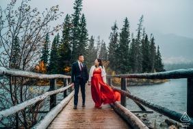 Pyramid Island, Jasper National Park, AB, Canadá fora da floresta, sessão de fotos antes do dia do casamento, enquanto cruzava uma ponte molhada sobre a água em uma tarde chuvosa