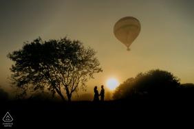 Boituva mini séance photo de couple avant le jour du mariage avec une montgolfière solo prenant son envol derrière eux